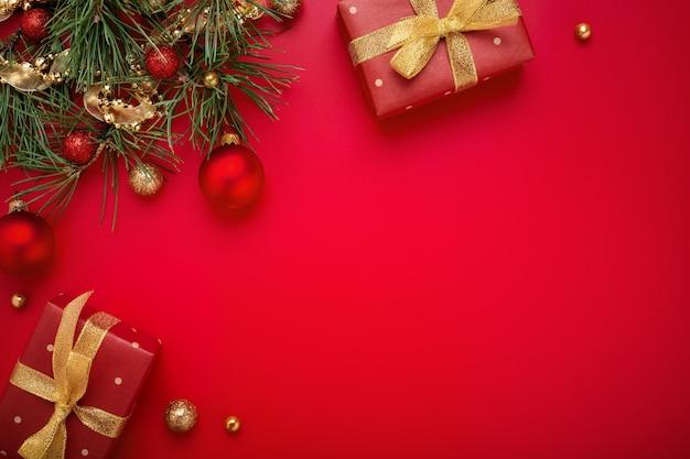 Regalos de navidad rojos y abeto con adornos de oro sobre fondo de espacio de copia.