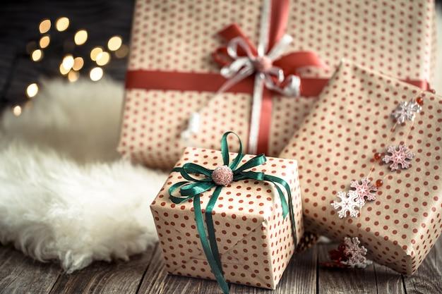 Regalos de navidad sobre luces en la mesa oscura sobre alfombra acogedora. decoraciones navideñas