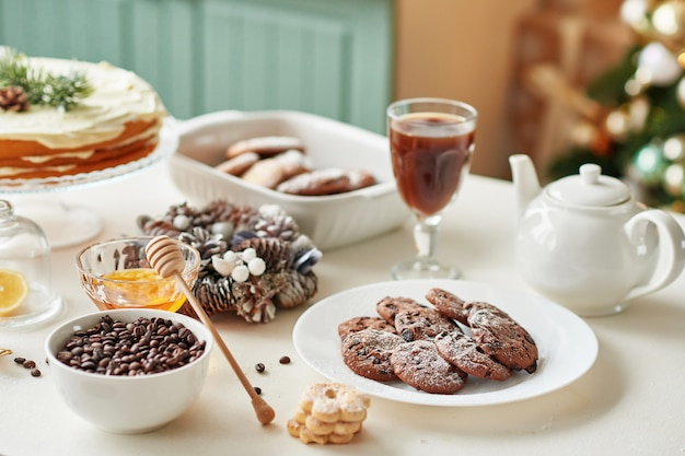 Regalos navideños sobre la mesa: magdalenas, pastel desnudo, galletas y café con miel