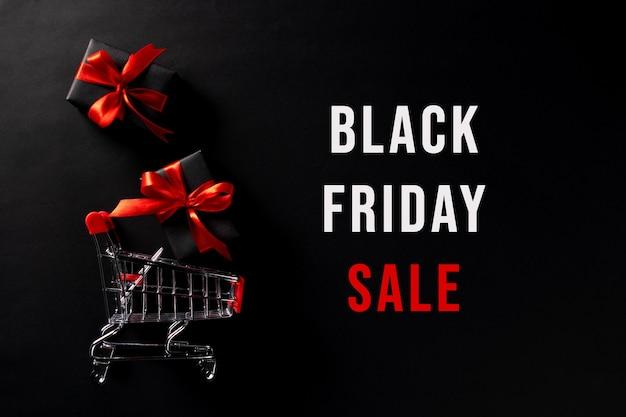 Regalos negros y carro de compras con texto venta de viernes negro.
