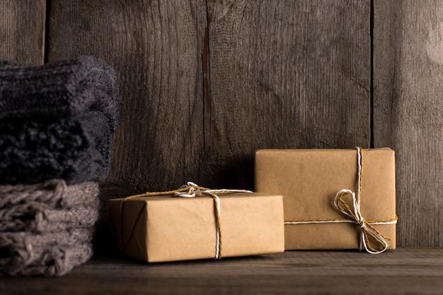 Regalos en papel artesanal en un viejo estante de madera, junto a bufandas tejidas.