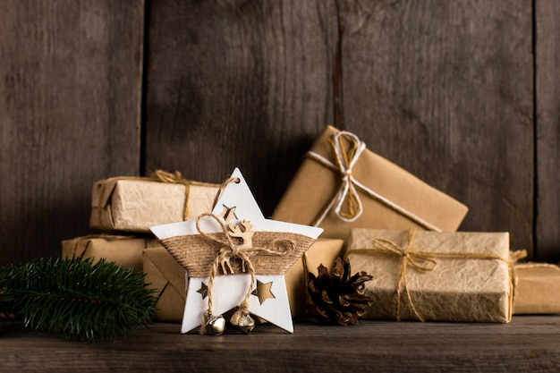 Regalos de papel kraft y una decoración de estrellas de navidad en una estantería de madera vieja.