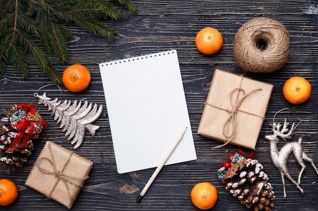Regalos, regalos y lista de deseos sobre fondo de madera oscura