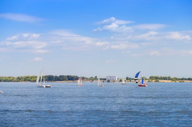 La regata de vela está en el río volga, cerca de la ciudad de volgogrado. muchos yates con velas en el agua.