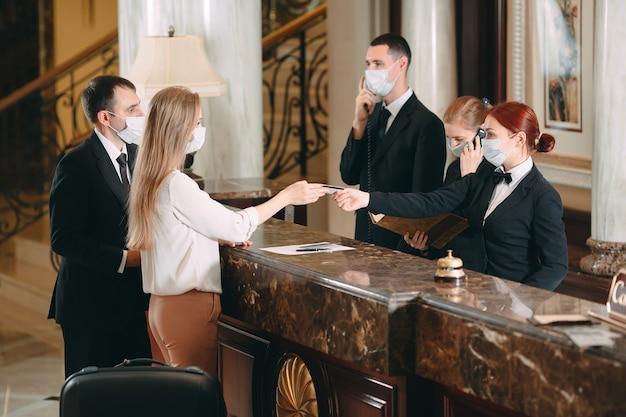 Registro en el hotel. recepcionista en el mostrador del hotel con máscaras médicas como precaución contra el virus. mujer joven en un viaje de negocios haciendo check-in en el hotel