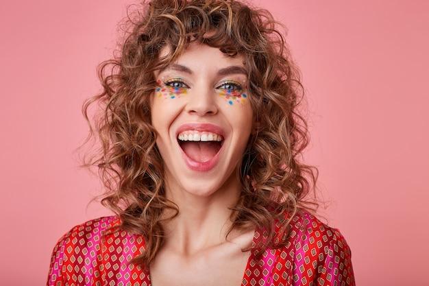 Regocijada joven mujer de ojos azules con cabello castaño rizado mirando felizmente y riendo con la boca abierta, aislada en la parte superior estampada de colores