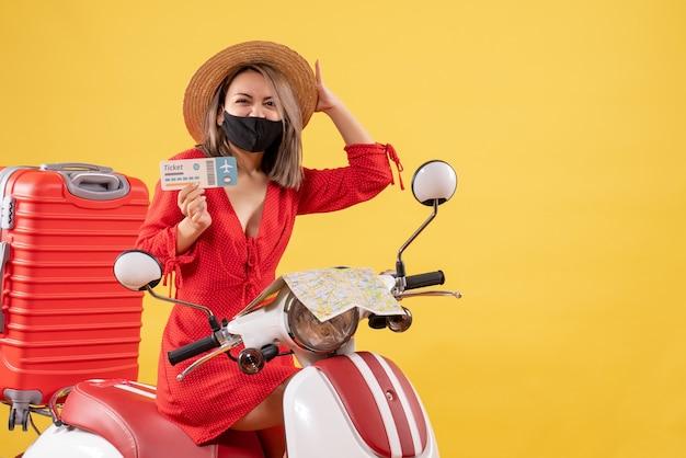Se regocijó señorita con máscara negra en ciclomotor con maleta roja sosteniendo el boleto
