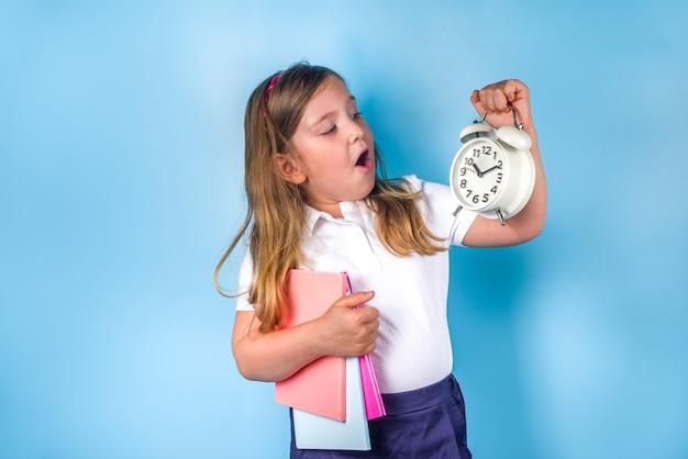 Regreso a la escuela, invitación, banner publicitario. muchacha linda del estudiante de la escuela primaria en uniforme azul blanco, con libros, despertador. tiempo para aprender, concepto de venta escolar