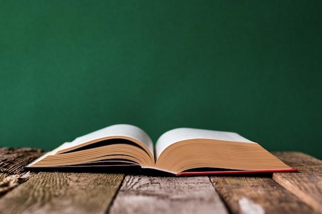 Regreso a la escuela con libro abierto sobre superficie de madera vieja