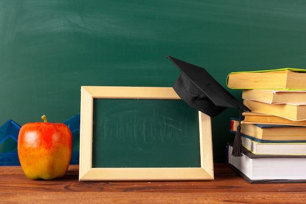 Regreso a la escuela: manzana y libros con lápices y pizarra