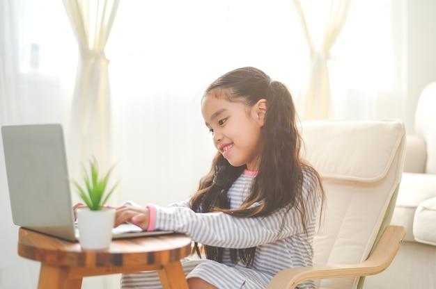 Regreso a la escuela, niña asiática que usa su computadora portátil