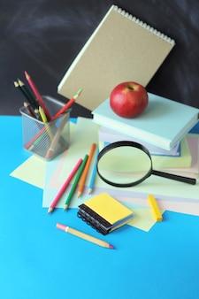 Regreso a la escuela, pila de libros, lupa y papelería en la mesa