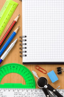 Regreso a la escuela y útiles cerca del cuaderno comprobado en textura de fondo de madera