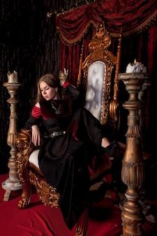 Reina medieval en traje histórico en el trono dorado en el castillo. retrato de mujer joven con un vestido de estilo antiguo en un trono antiguo en la sala de recepción de la fortaleza. concepto de eventos de disfraces temáticos.