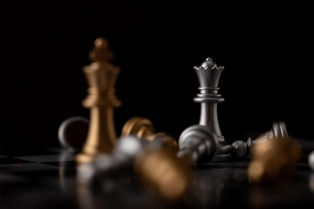 Reina y rey de pie en medio de la caída del ajedrez.