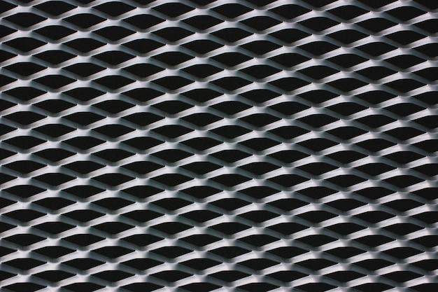 Rejilla de malla de alambre de acero en la parte delantera del edificio. textura blanco y negro