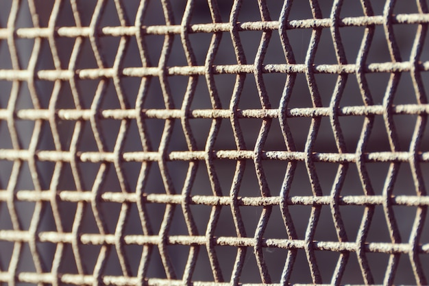 Rejilla oxidada de cerca sobre un fondo oscuro