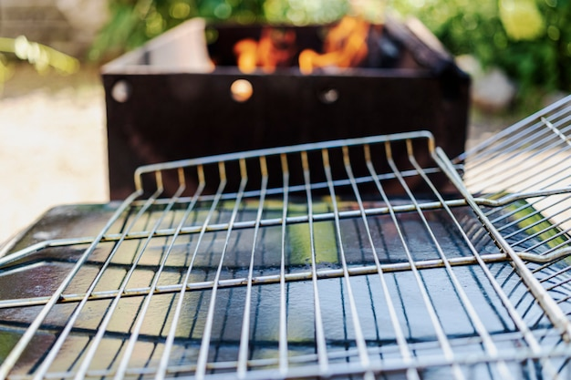 Una rejilla de parrilla vacía en el fondo de una barbacoa preparada para forrar carne o verduras. descanse en la naturaleza.