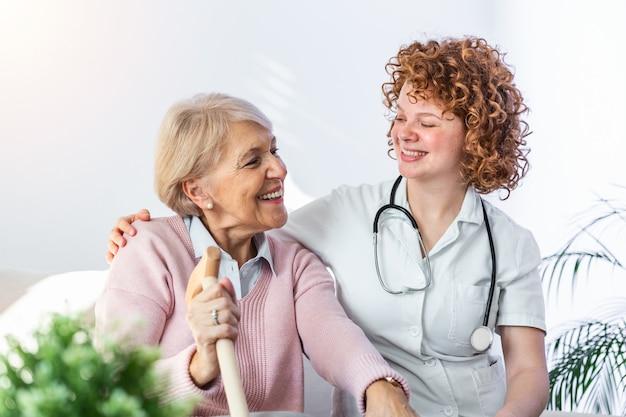 Relación amistosa entre cuidador sonriente en uniforme y feliz anciana.
