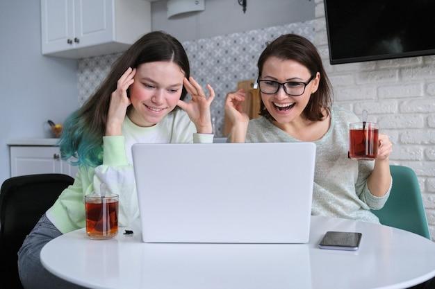 Relaciones entre madre e hija adolescente, padre y adolescente sentados en casa en la cocina bebiendo té juntos y mirando el monitor de la computadora portátil