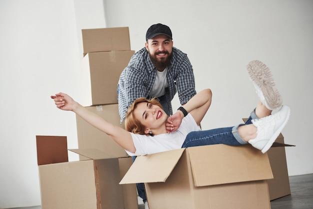 Relajación al sentarse en la caja vacía. pareja feliz juntos en su nueva casa. concepción de mudanza