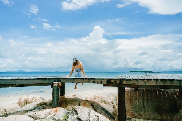 Relajación despreocupada mujer sentada en el puente de madera