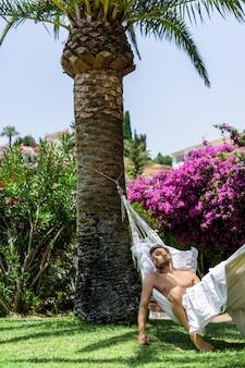 Relajación masculina desnuda en una hamaca en el jardín.