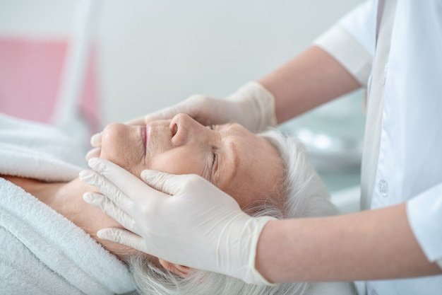 Relajación. mujer madura de pelo gris acostado con los ojos cerrados con un masaje facial