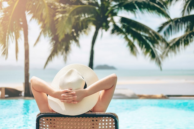 Relajación de la mujer sin preocupaciones en la piscina concepto de vacaciones de verano
