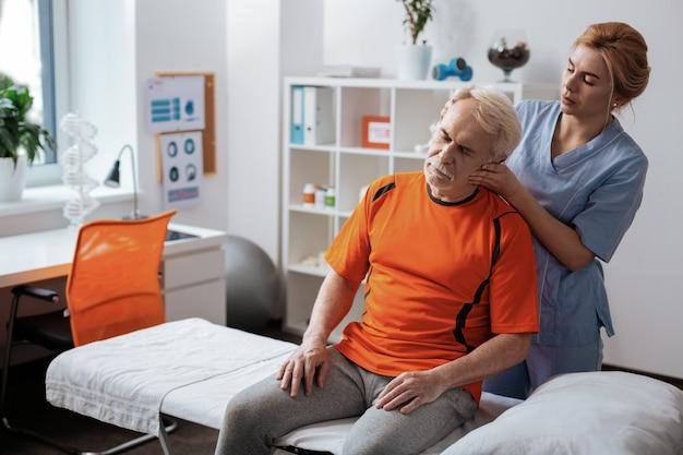 Relajación de músculos. agradable hombre mayor sentado frente a la enfermera mientras recibe un masaje de cabeza profesional