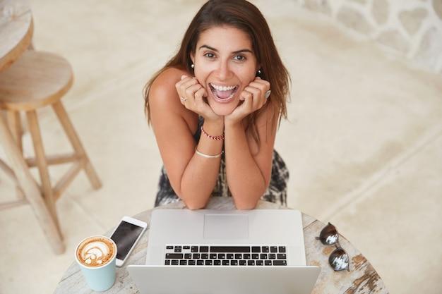 Relajada y alegre trabajadora independiente trabaja en el proyecto de los clientes, actualiza el software, trabaja en la cafetería, está conectada a internet inalámbrico.