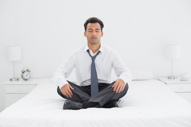 Relajado hombre bien vestido sentado con los ojos cerrados en la cama