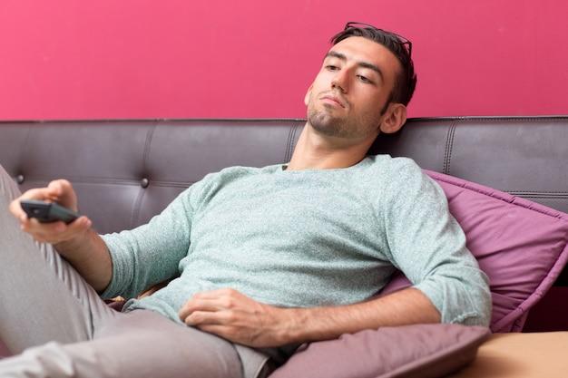 Relajado, joven, guapo, hombre, mirar, televisión, hogar