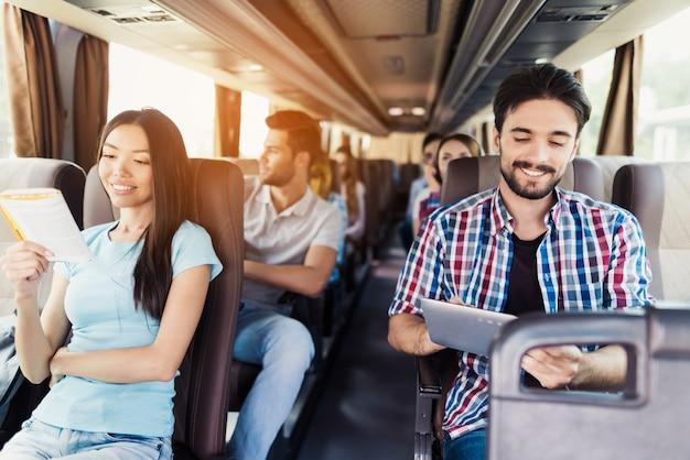 Relajados jóvenes pasajeros en bus turístico de viaje.
