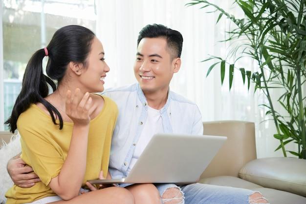 Relajante pareja usando laptop en sofá