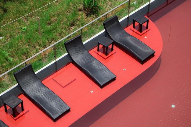 Relajantes sillas de ratán negro al lado de la piscina