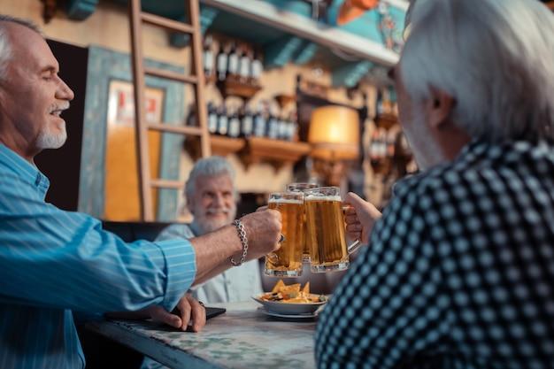 Relajarse y beber. tres hombres canosos que se sienten increíbles mientras se relajan y beben cerveza
