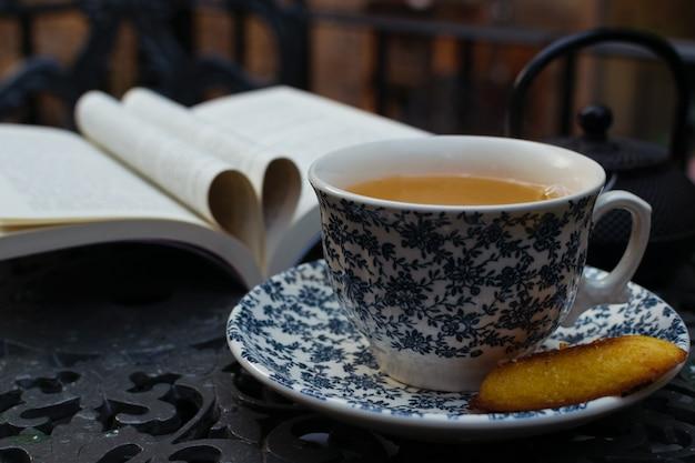 Relajarse la hora del té y leer en el porche en una mesa de hierro. libro del día mundial