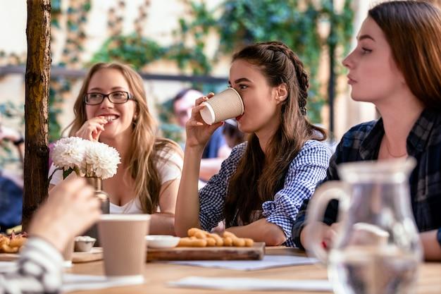 Relajarse con los mejores amigos en la terraza de un café local en los días calurosos y soleados