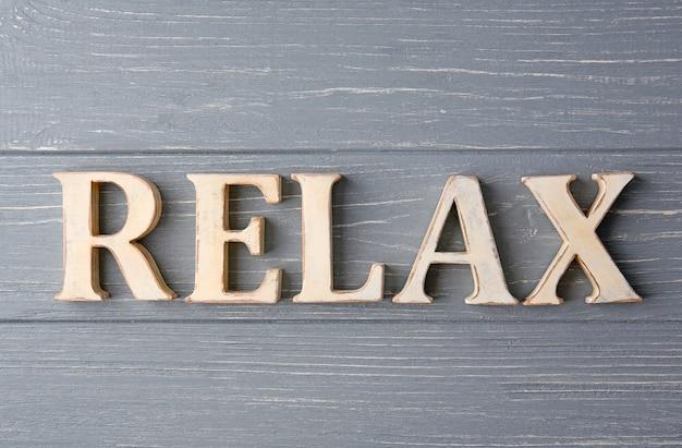 Relajarse palabra hecha de letras sobre superficie de madera