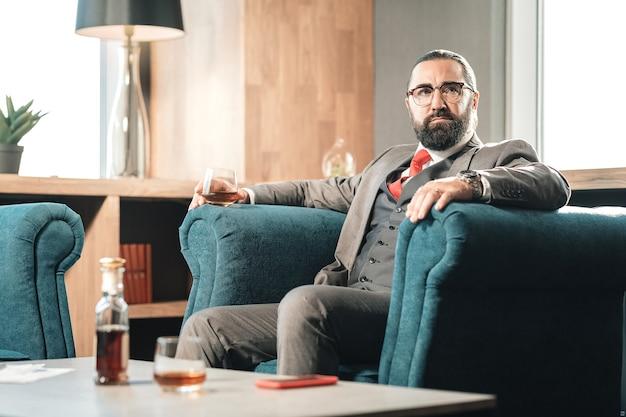 Relájate después del trabajo. famoso abogado rico que se relaja después de un día duro y nervioso sosteniendo una copa de coñac