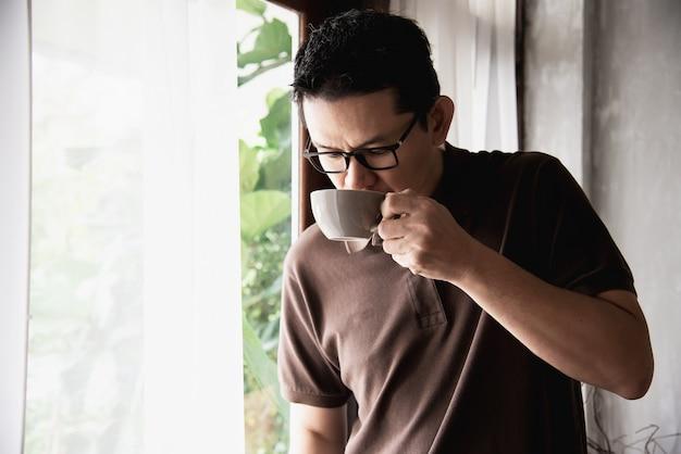 Relaje al hombre asiático que bebe un café