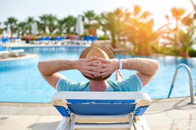 Relájese en la piscina de verano. hombre joven y acertado que miente en una tumbona del sol en el hotel en el fondo de la puesta del sol, tiempo del concepto para viajar