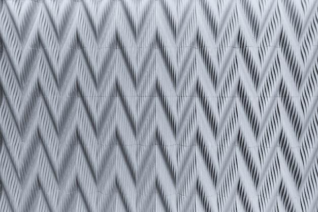 Relieve de baldosas de hormigón gris decorativo en zigzag en la pared. patrón convexo