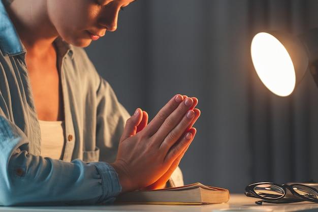 Religión mujer cruzó las manos en oración. orar con la biblia al atardecer en casa y recurrir a dios, pedir perdón y creer en la bondad.