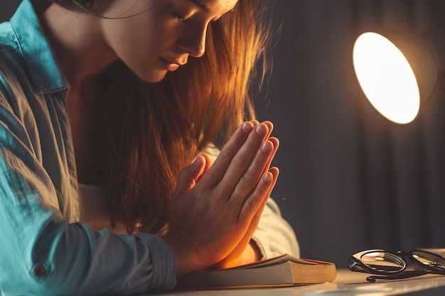 Religión mujer rezando con la biblia en la noche en casa y recurrir a dios, pedir perdón y creer en la bondad. vida cristiana y fe en dios