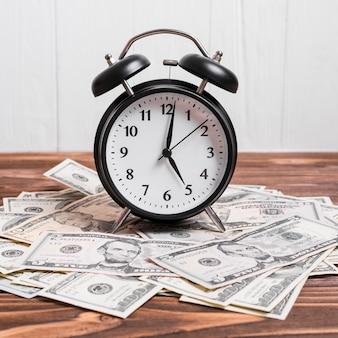 Un reloj de alarma en billetes de la moneda sobre la mesa de madera