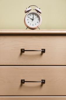 Un reloj de alarma encima de un gabinete de madera.