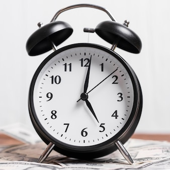 Un reloj de alarma sobre billetes.