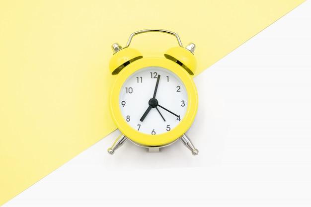 Reloj amarillo sobre amarillo y blanco.